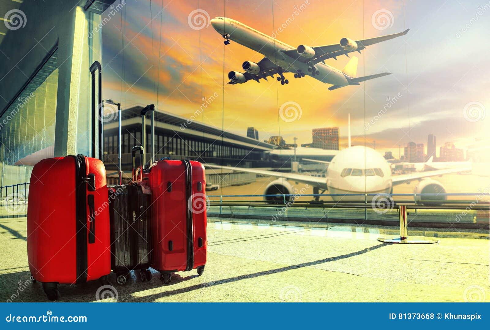 A bagagem de viagem na construção terminal de aeroporto e o plano de jato voam