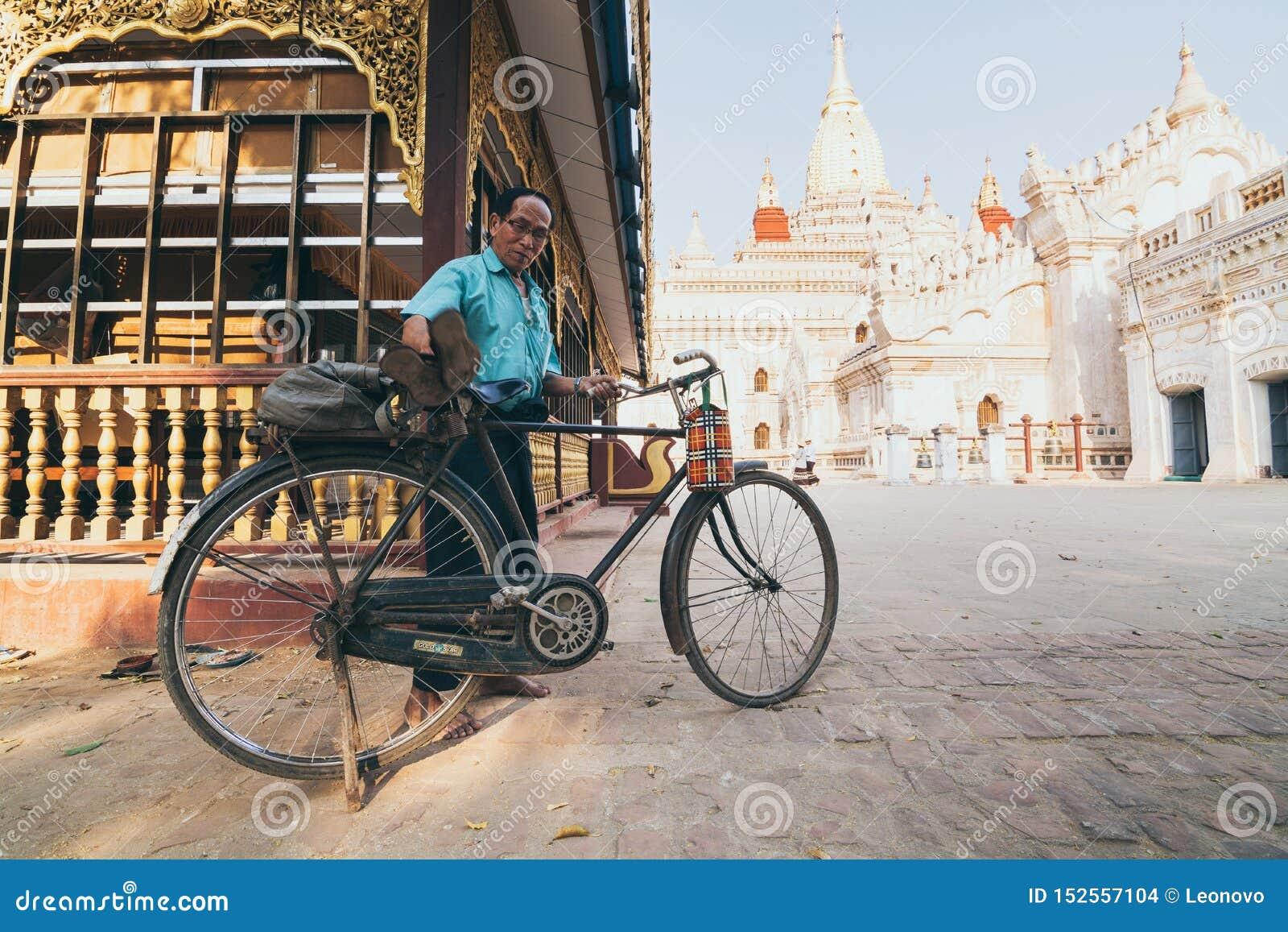 Bagan, Myanmar - March 2019: Burmese man parking bicycle in the backyard of Ananda temple
