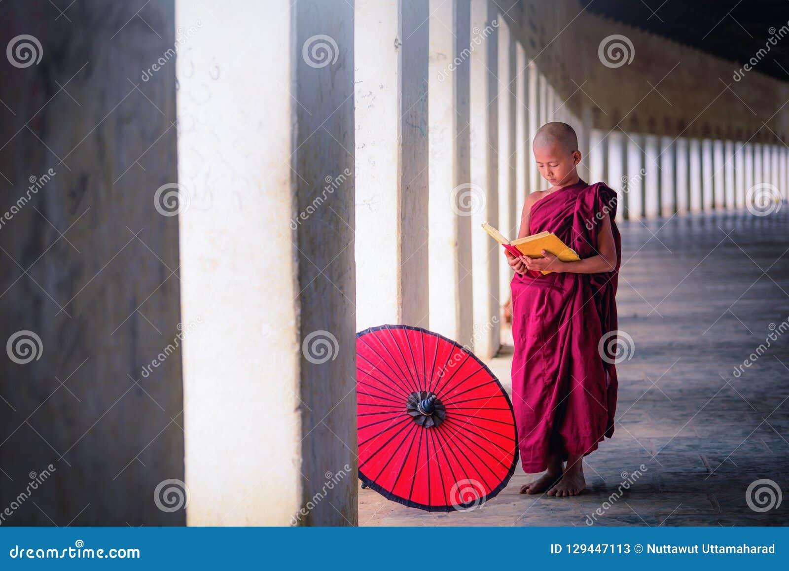 Bagan, Myanmar, o 9 de dezembro de 2017: Monge budista nova le do principiante