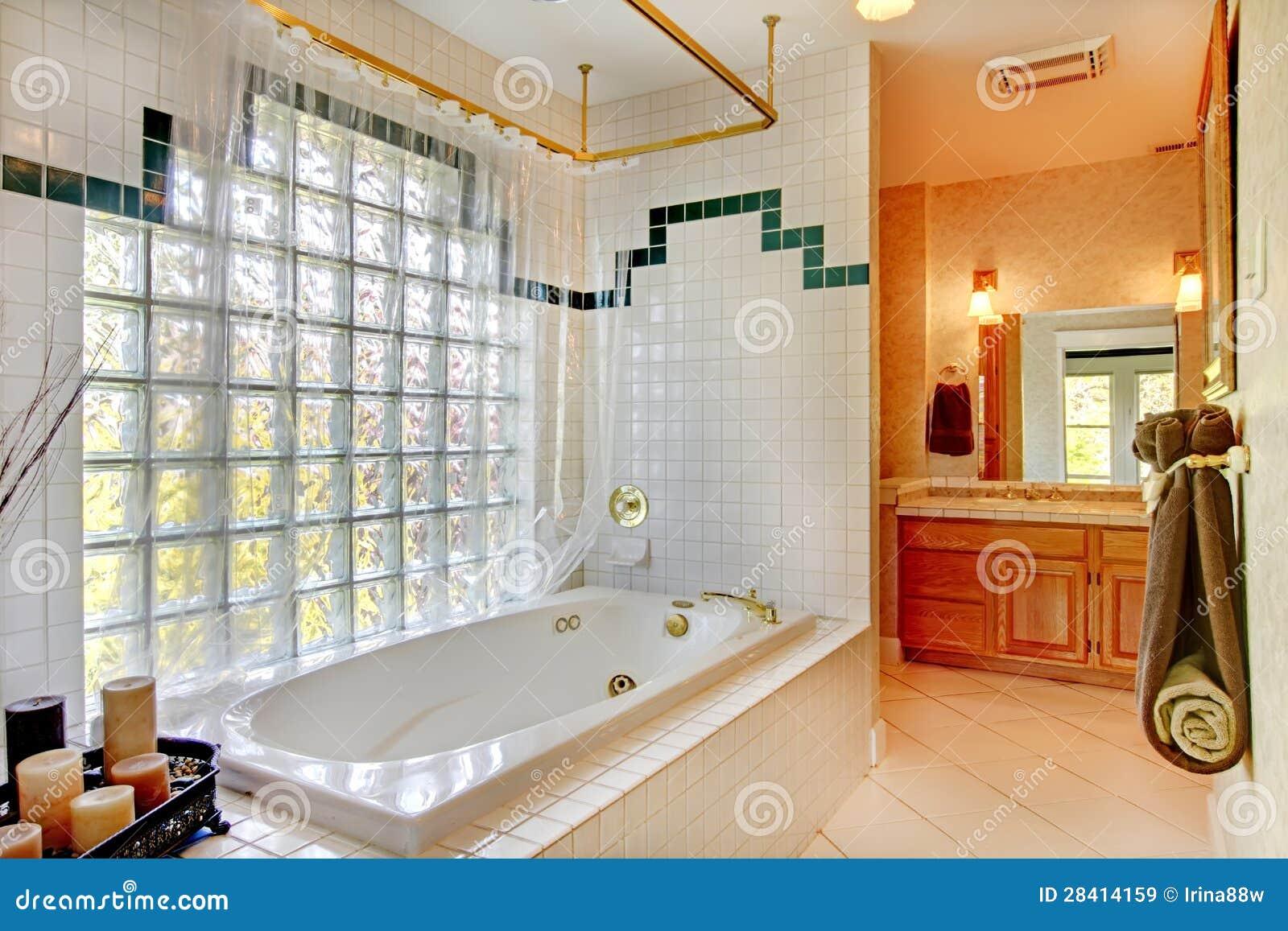 Bagno con la parete di vetro e la vasca. con i gabinetti e la candela ...