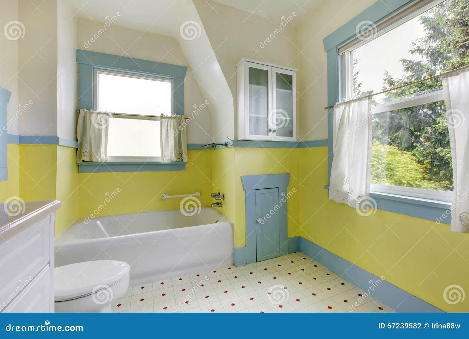Bagno con le pareti gialle la pavimentazione in piastrelle bianca
