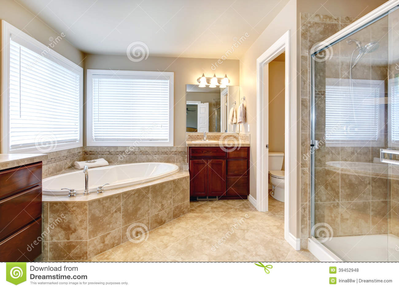 Bagno beige con le finestre, i gabinetti di legno della ciliegia, la ...