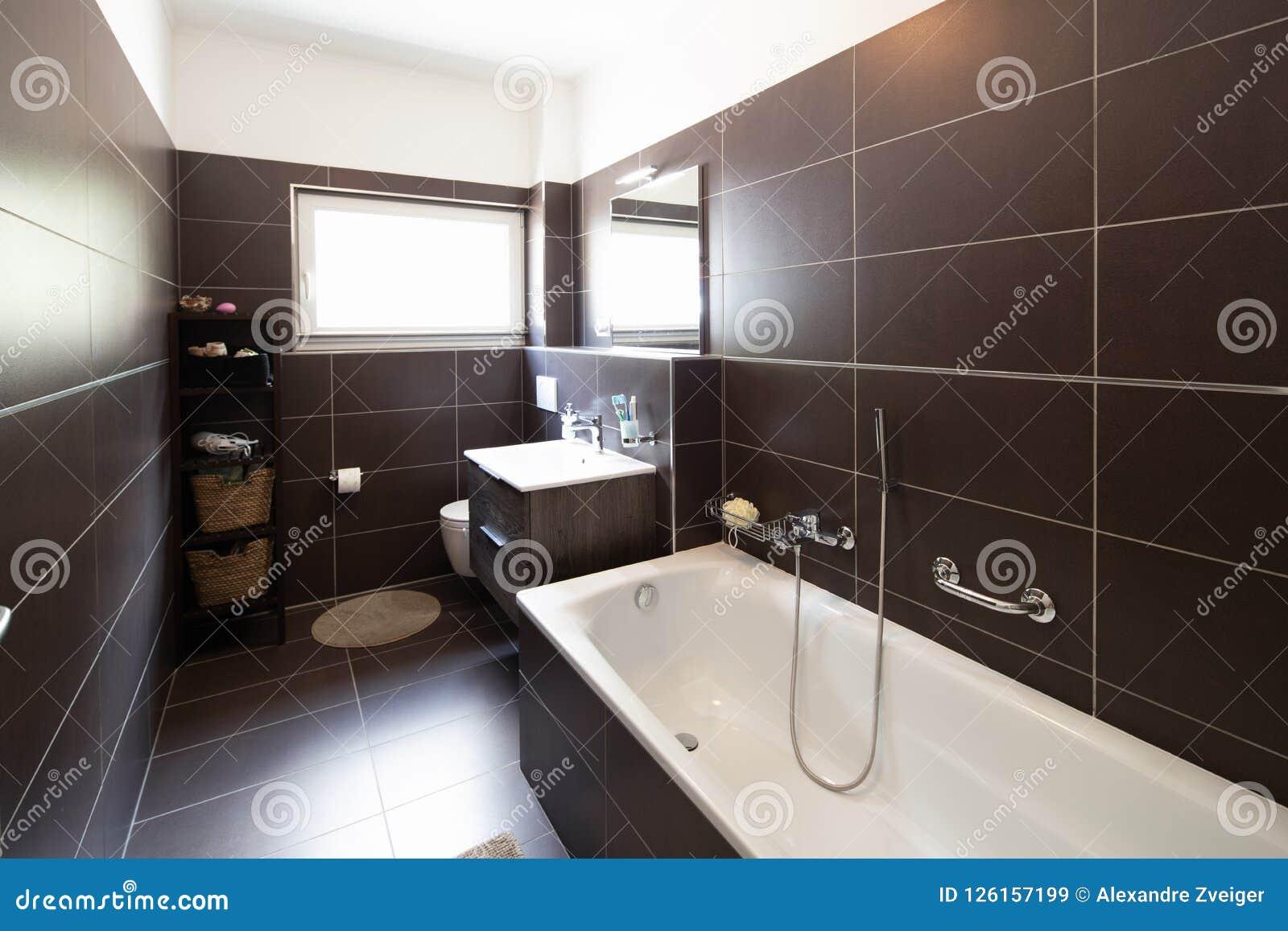 Bagno moderno con le mattonelle e la finestra marroni