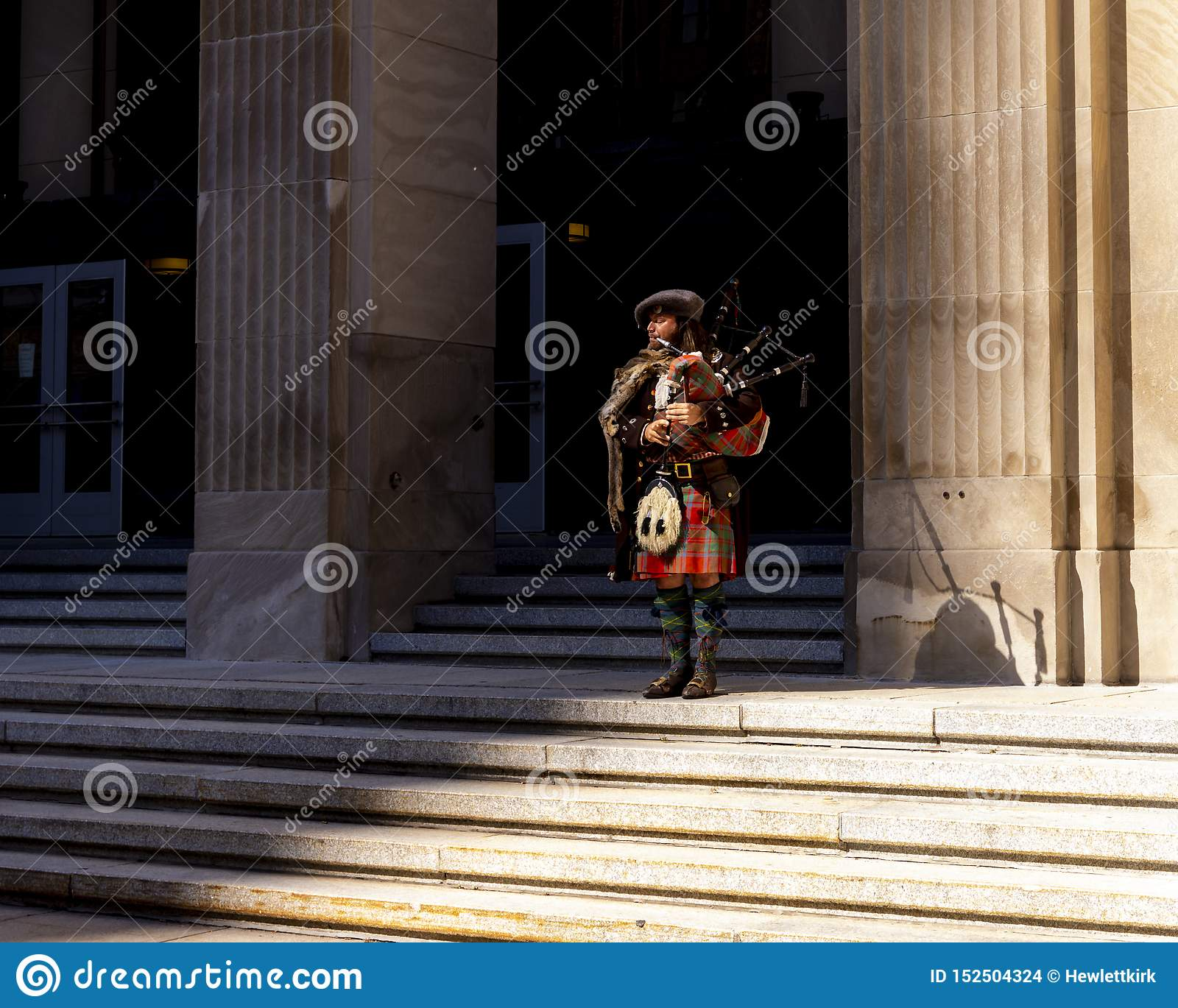 Bagpiper performing on building steps