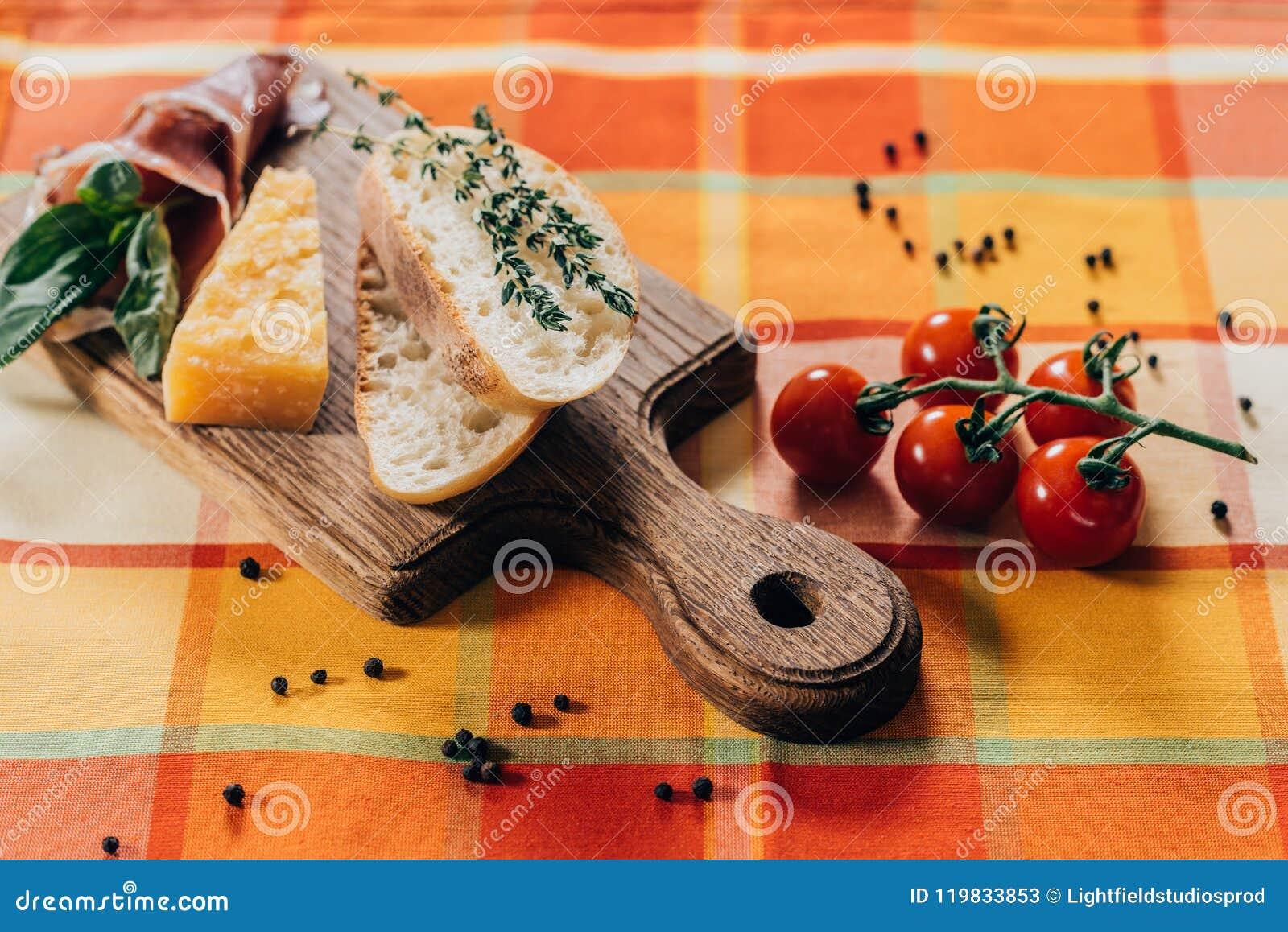 Baguette, carne e parmigiano affettati sul tagliere di legno e sui pomodori ciliegia freschi