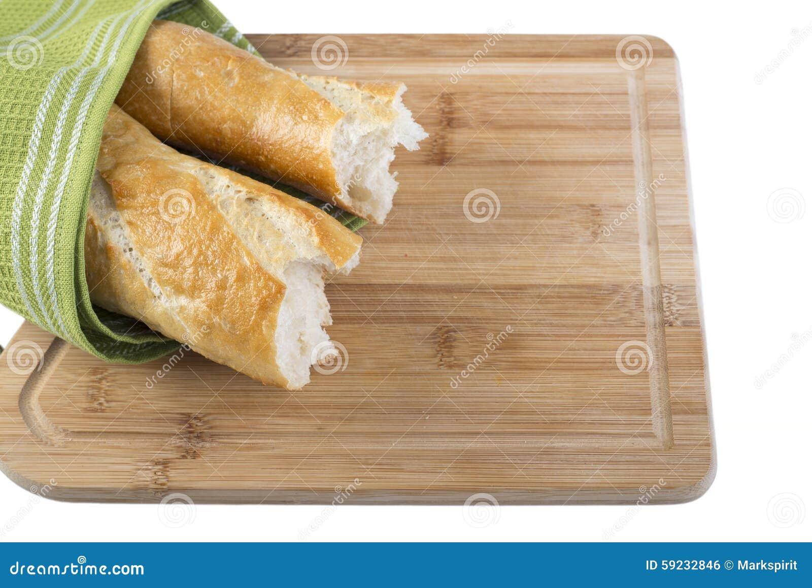 Baguette largo roto en pedazos en el fondo blanco