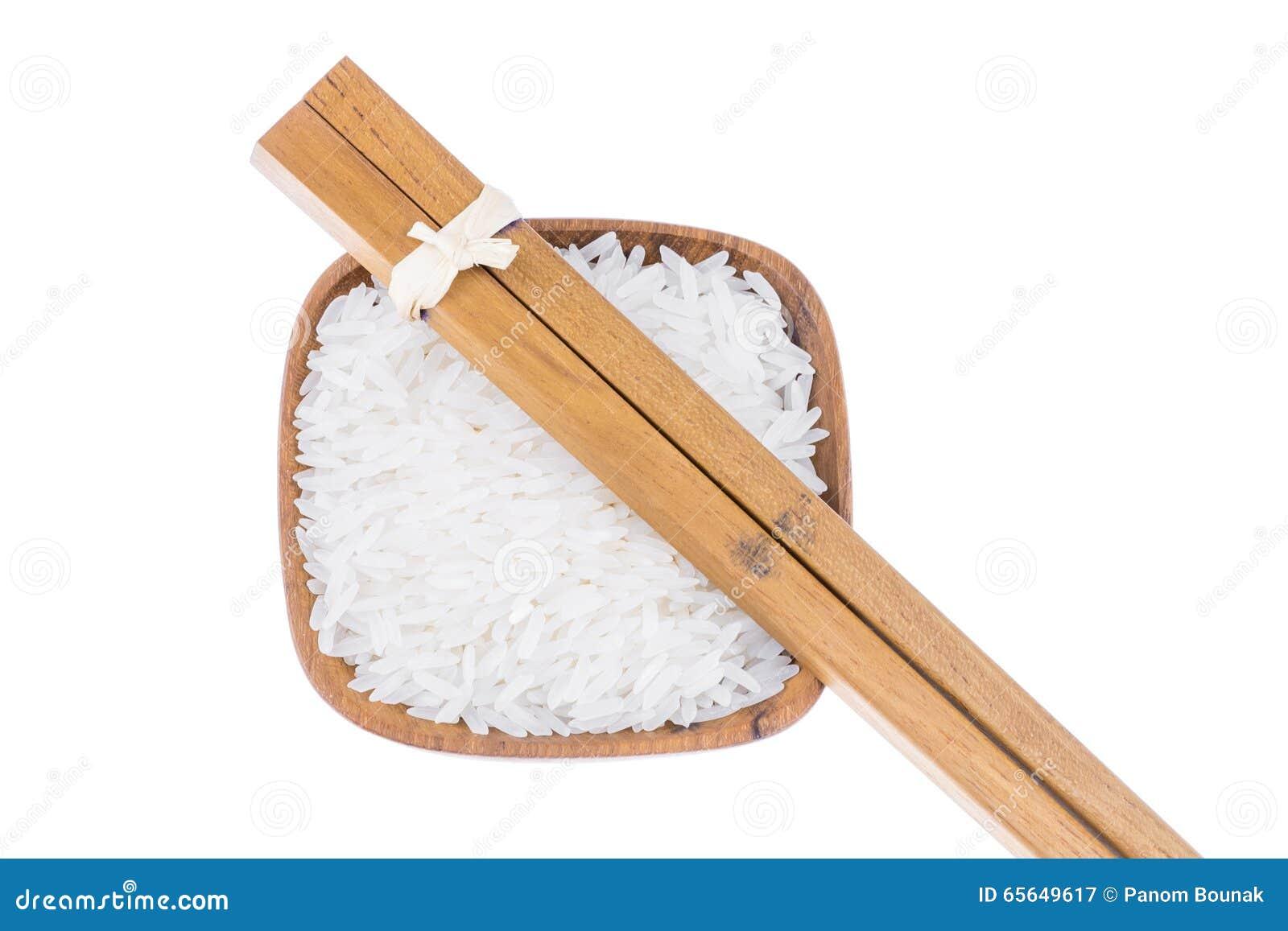 Baguettes en bois naturelles avec du riz dans la petite cuvette en bois