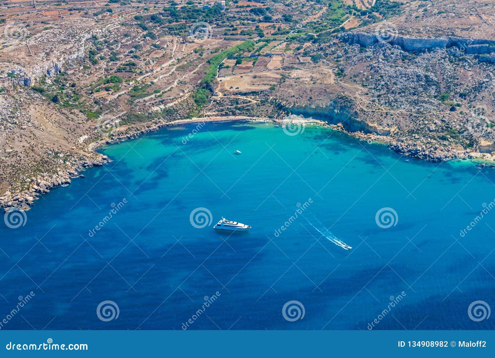 Bahía de Mgiebah, ensenada aislada accesible por una trayectoria escarpada, rocosa, con una playa arenosa y un agua de azules tur