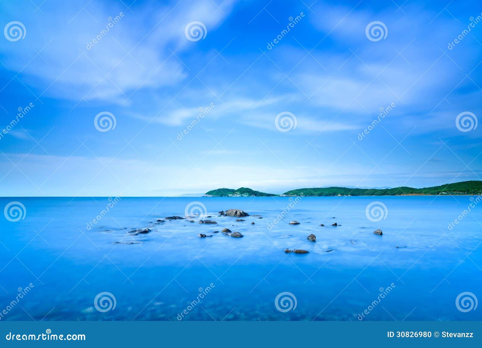 Baia di Baratti, piccole rocce in un oceano blu sul tramonto. La Toscana, Italia.