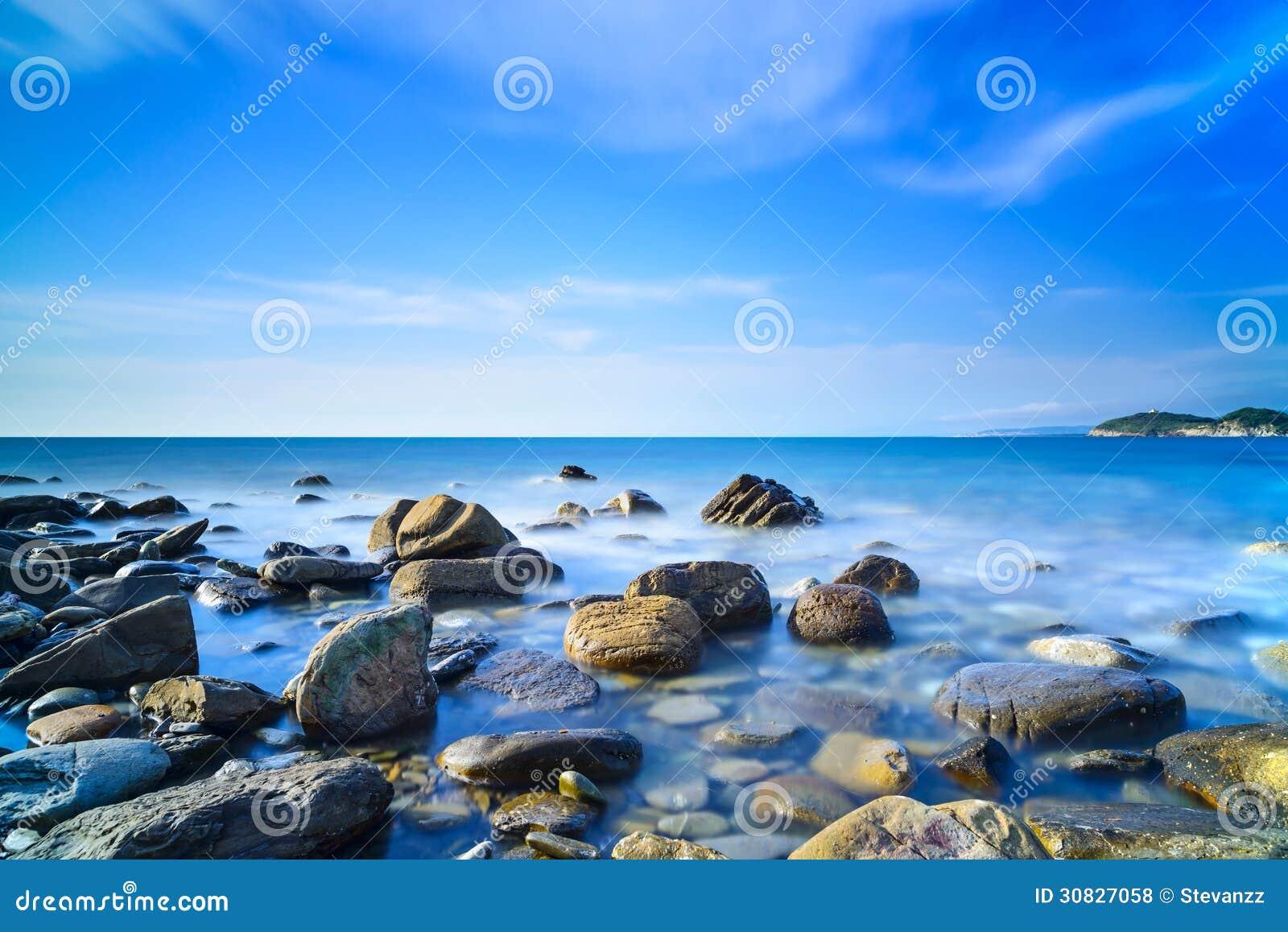 Baia di Baratti, rocce in un oceano blu sul tramonto. La Toscana, Italia.