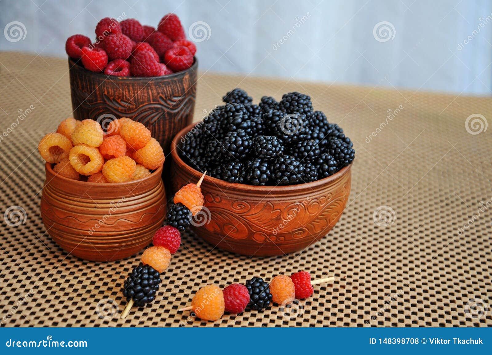 Baies color?es des framboises rouges, jaunes et noires ou des m?res en poterie de terre