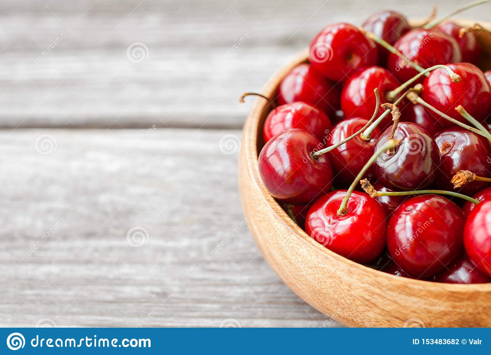 Baies mûres rouges de cerise dans la cuvette en bois Fond de nourriture
