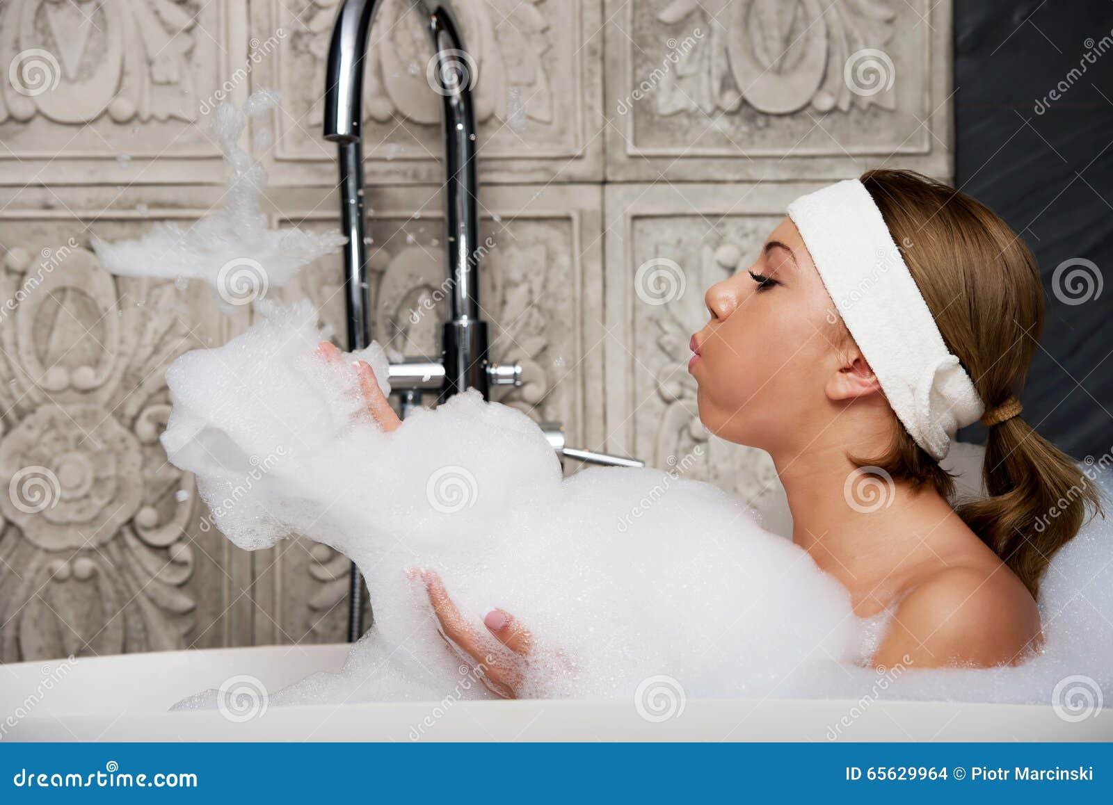 Baigner la femme détendant dans le bain