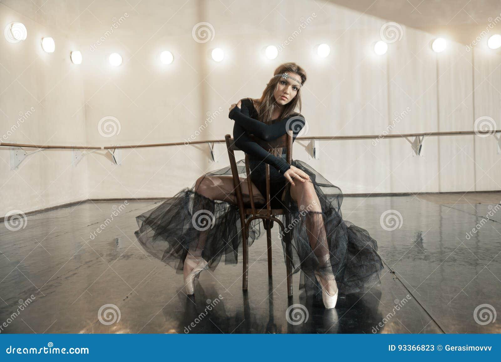 Bailarín de ballet contemporáneo en una silla de madera en una repetición