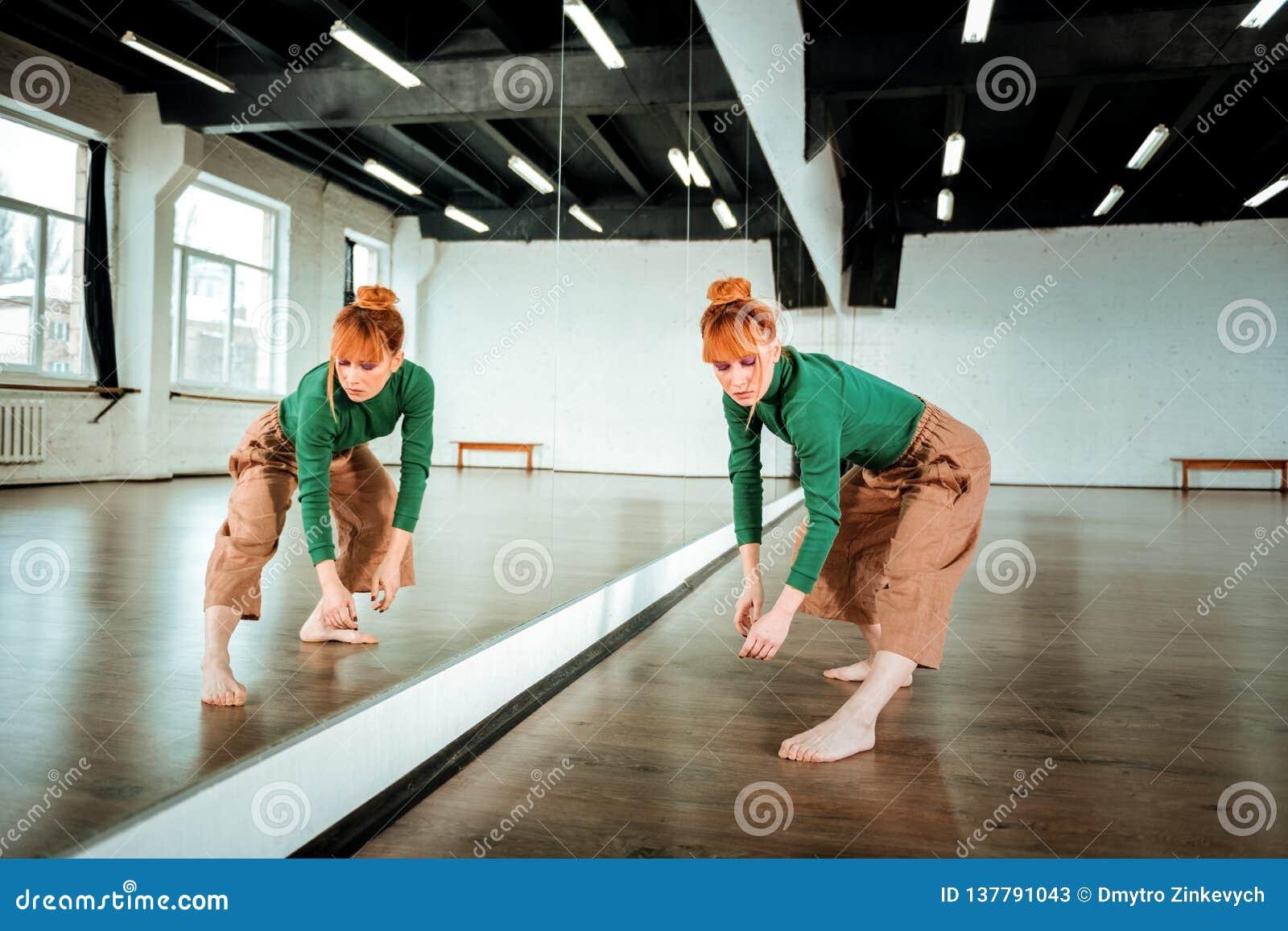 Bailarín profesional pelirrojo bonito en un cuello alto verde que parece concentrado