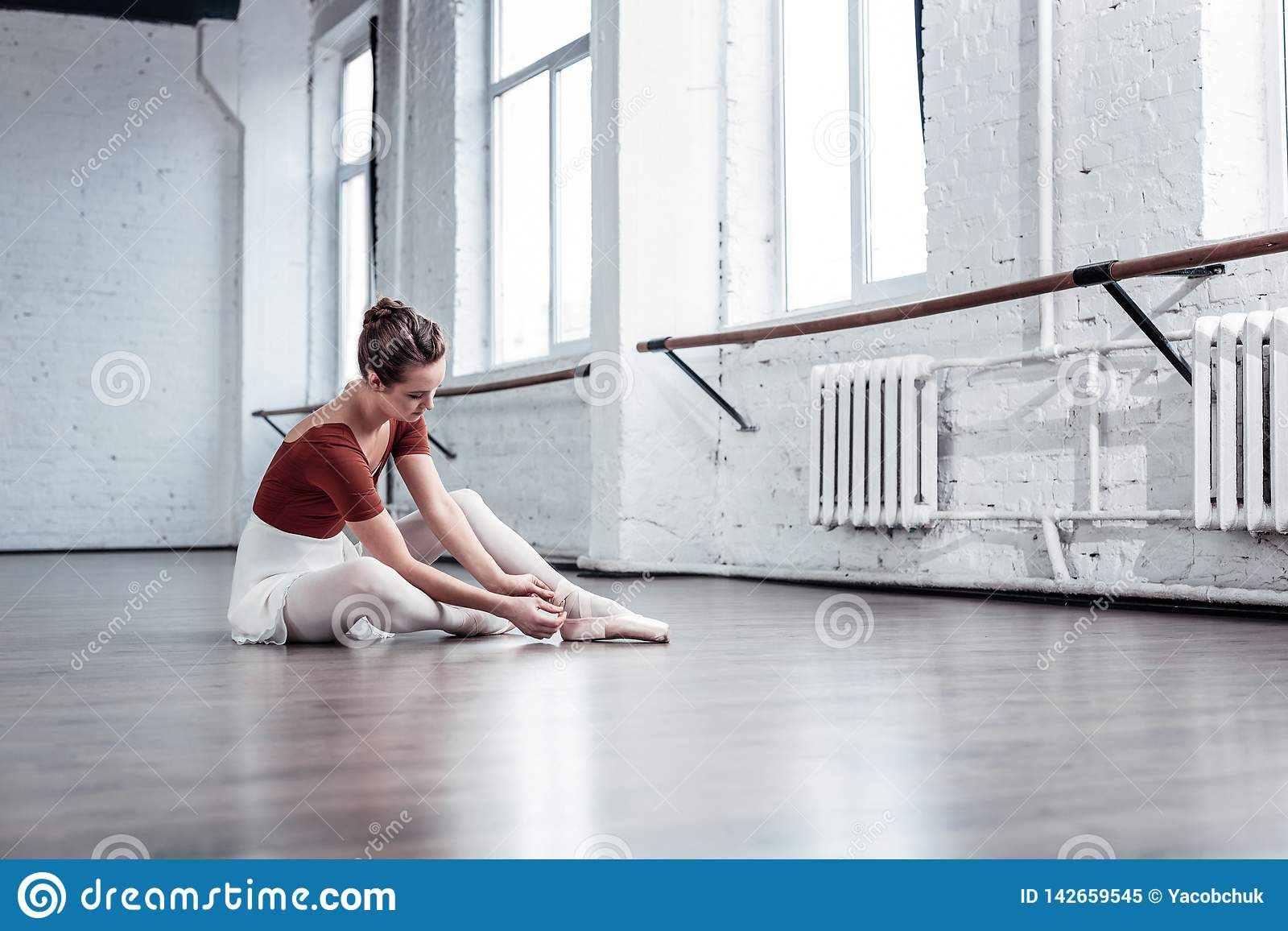 Bailarina agradável atrativa que senta-se no assoalho no estúdio da dança