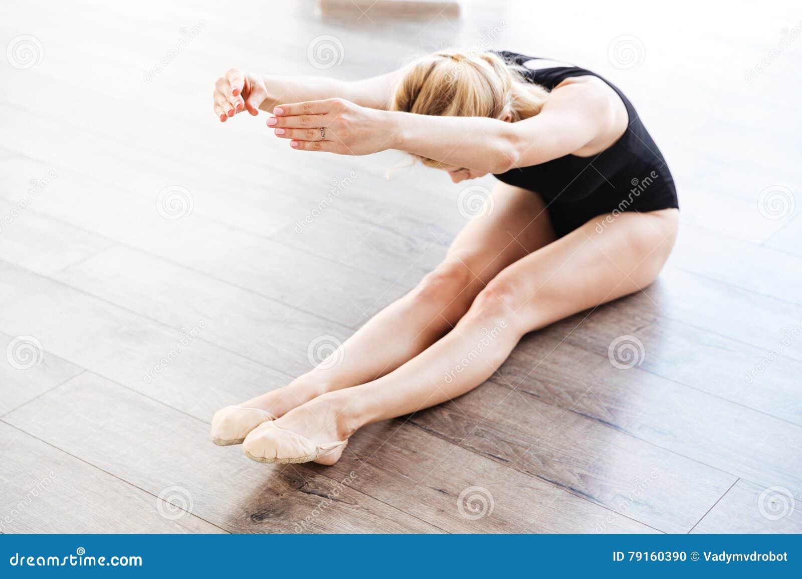 A bailarina bonita da jovem mulher que senta e que faz o esticão exercita