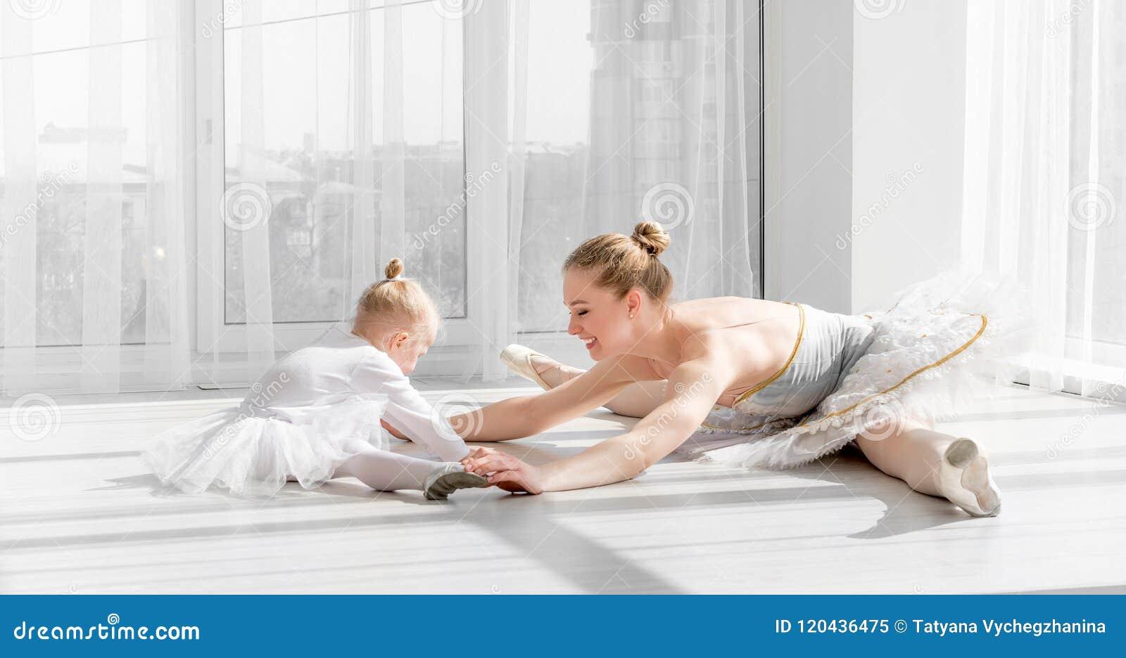 Bailarina com a menina da criança que aquece-se antes de treinar