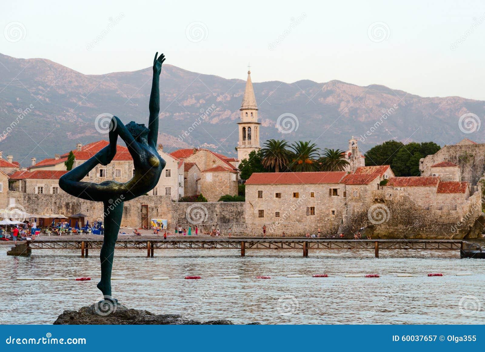 Bailarina da escultura (dançarino de Budva) contra o contexto da cidade velha