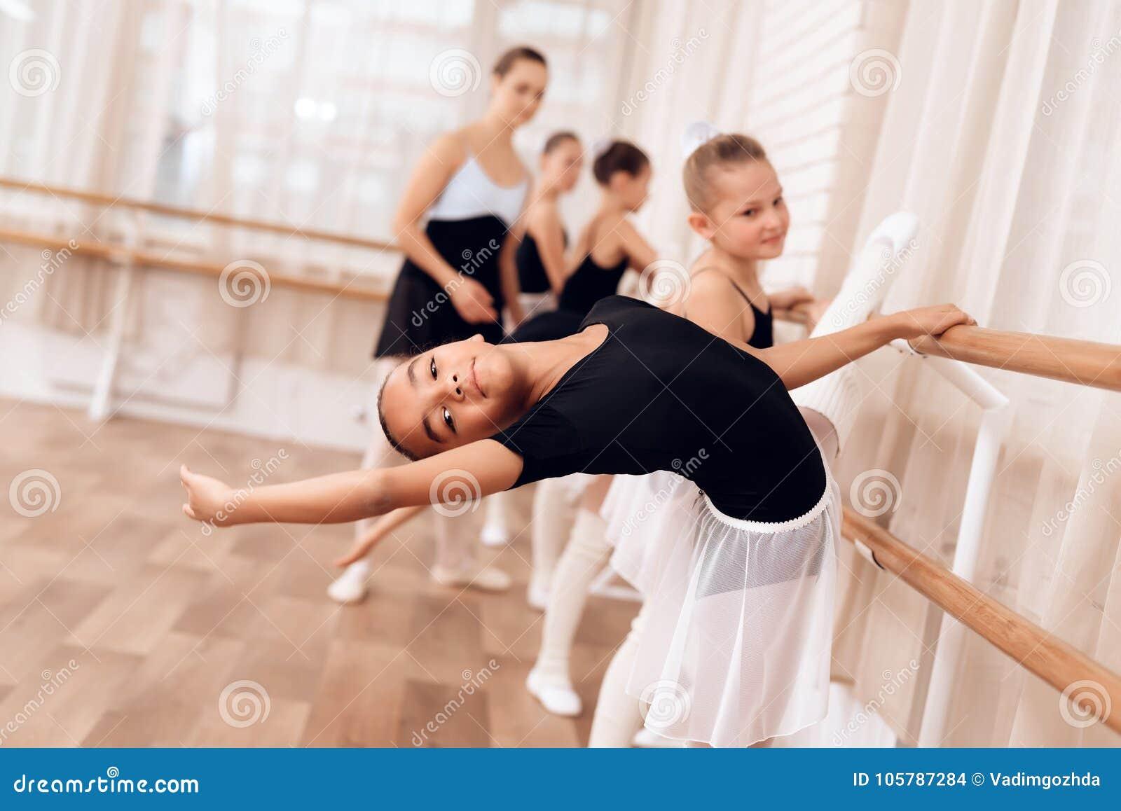 A bailarina nova faz um movimento da dança com suas mãos durante uma classe em uma escola do bailado