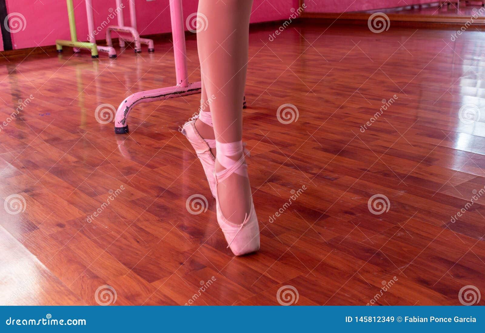 Bailarina que ensaia com seus deslizadores cor-de-rosa do bailado