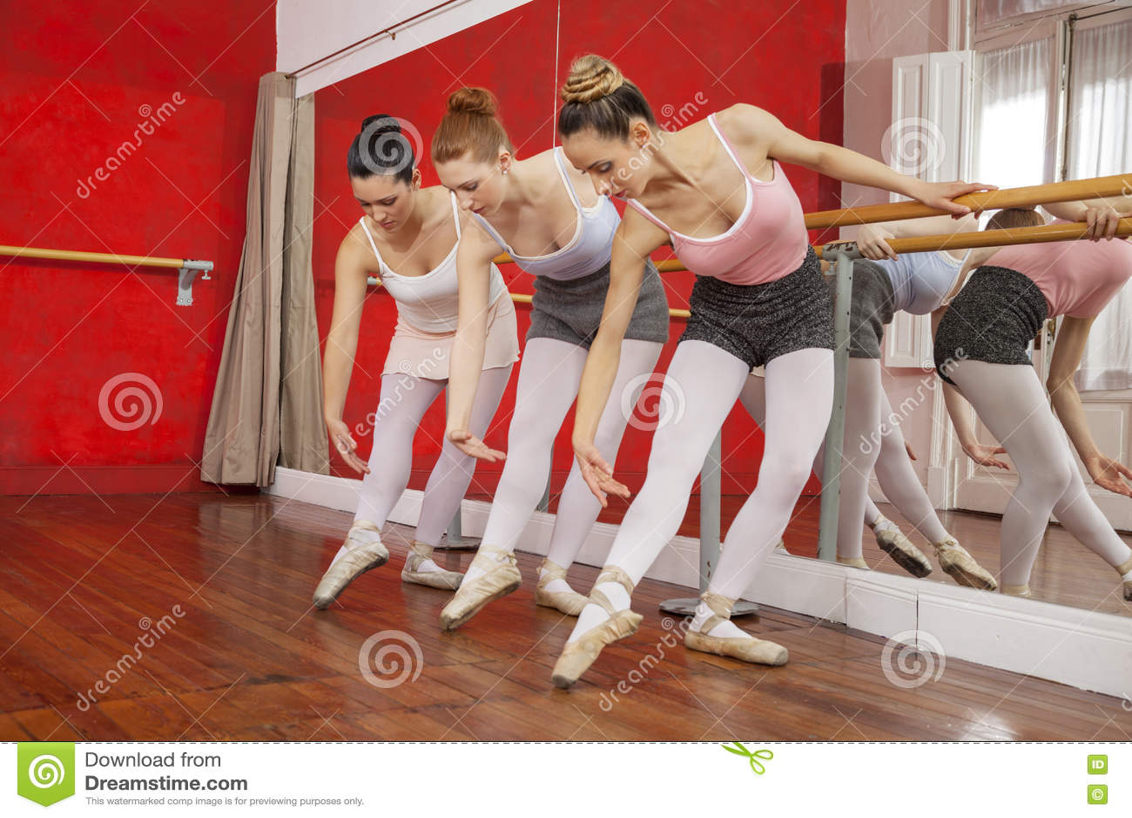 Bailarinas que dobram-se ao executar no estúdio de formação