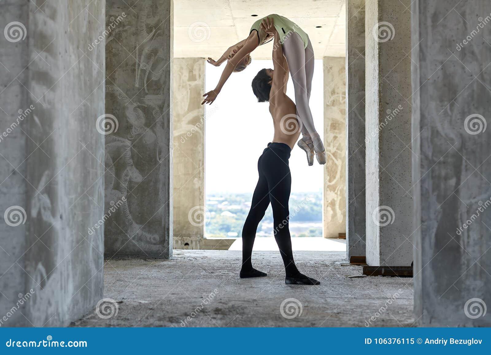 Bailarines de ballet que presentan en el edificio inacabado