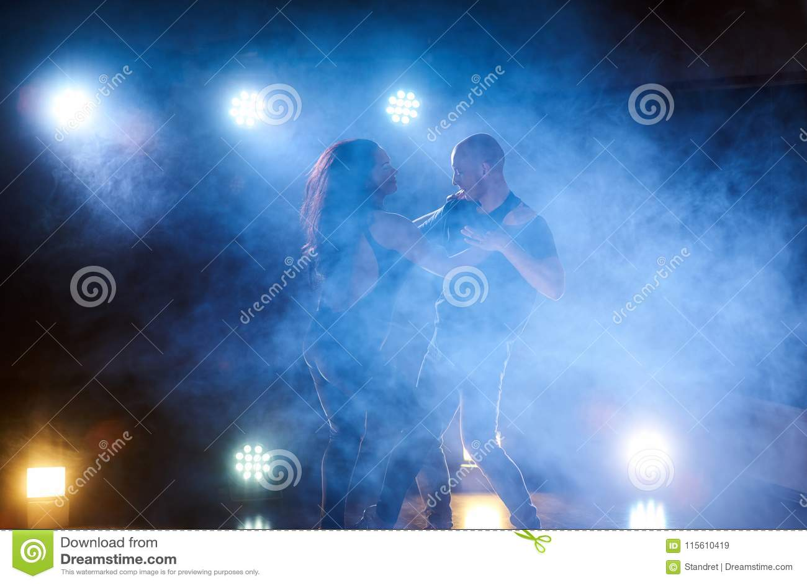 Bailarines expertos que se realizan en el cuarto oscuro debajo de la luz y del humo del concierto Pares sensuales que realizan un