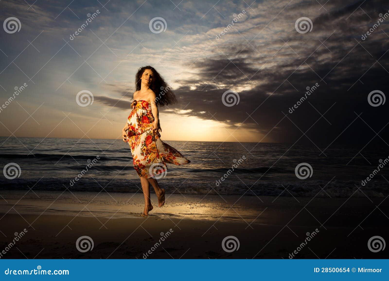 Baile de la mujer embarazada en la playa hermosa.