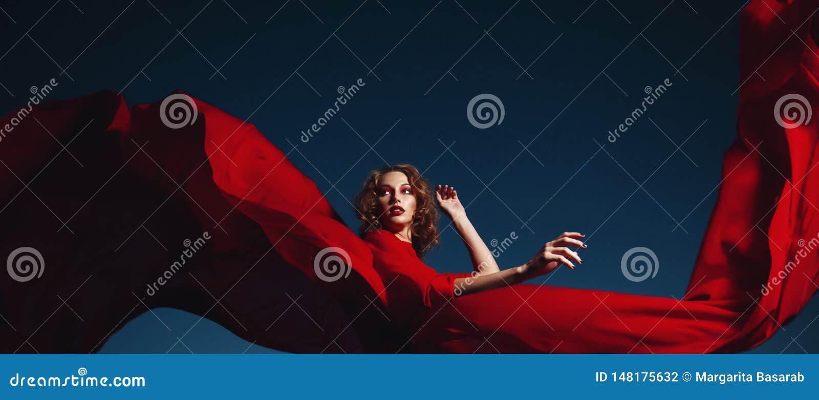 Baile de la mujer en el vestido de seda, la tela que agita y flittering del vestido que sopla rojo art?stico