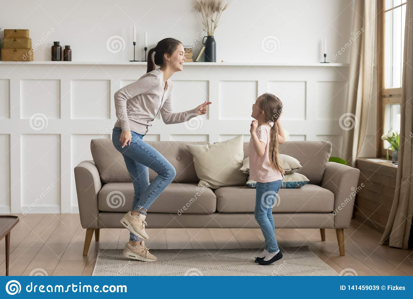 Baile de risa feliz de la hija de la mamá y del niño en casa