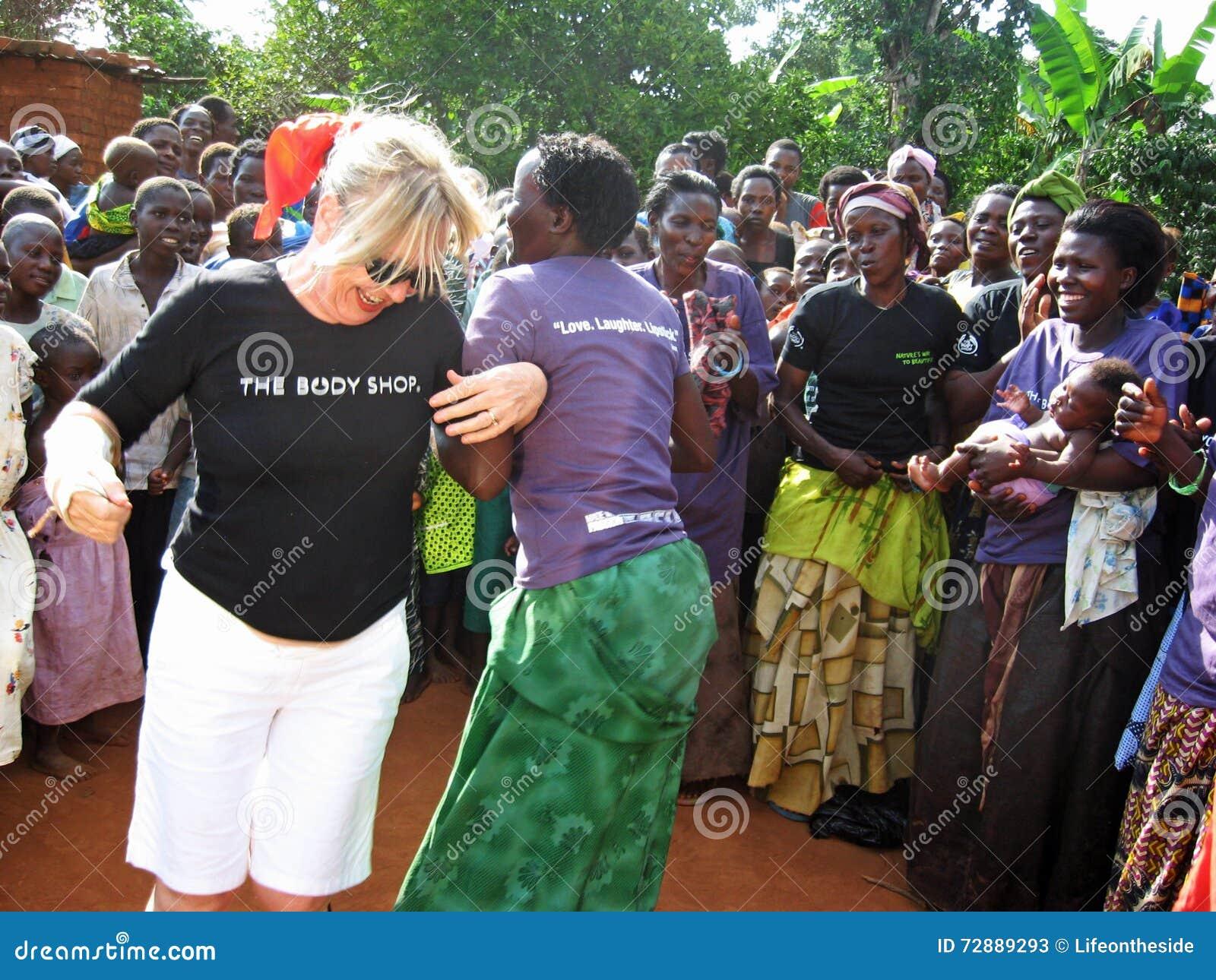 Baile del ayudante humanitario de la mujer africana y blanca para la alegría delante de los aldeanos Uganda África