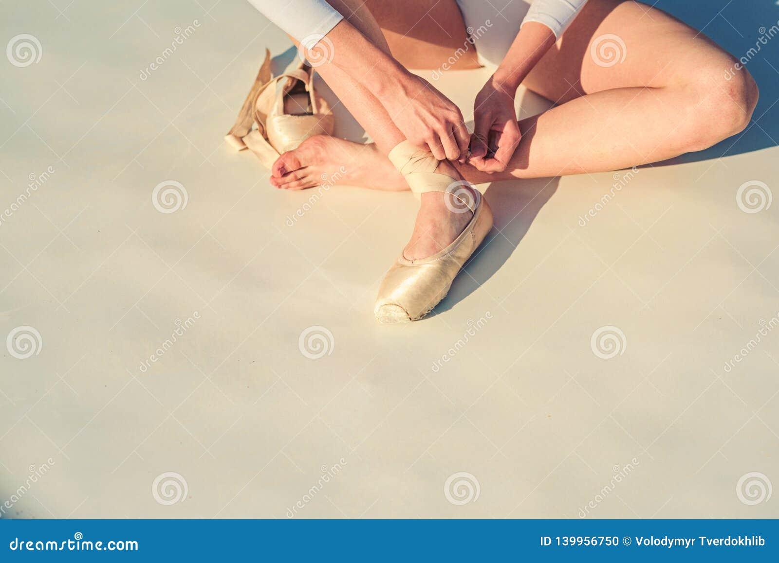 Baile en pointe Zapatos de la bailarina Piernas de la bailarina en los zapatos de ballet blancos Atadura de los deslizadores del