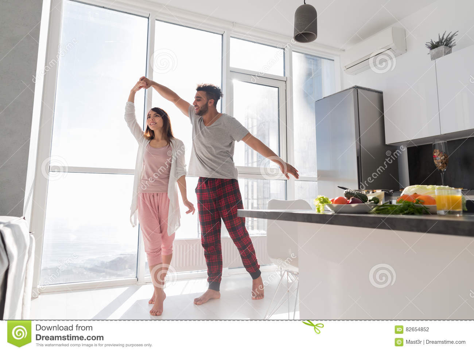 Baile joven de los pares en cocina, mujer asiática preciosa y hombre de los hispanos