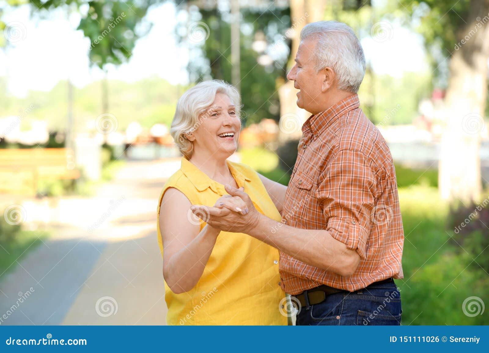 Baile maduro feliz de los pares al aire libre