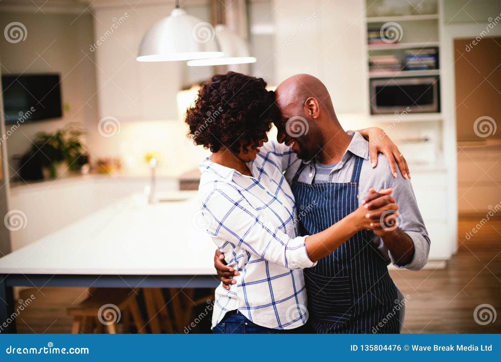 Baile romántico de los pares en cocina