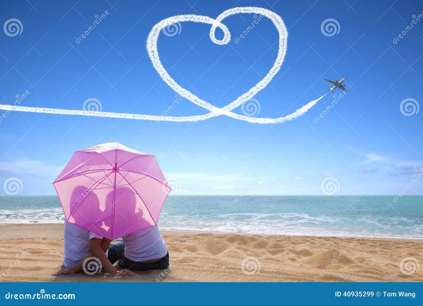 Baisers romantiques de jeunes couples à la plage avec le parapluie