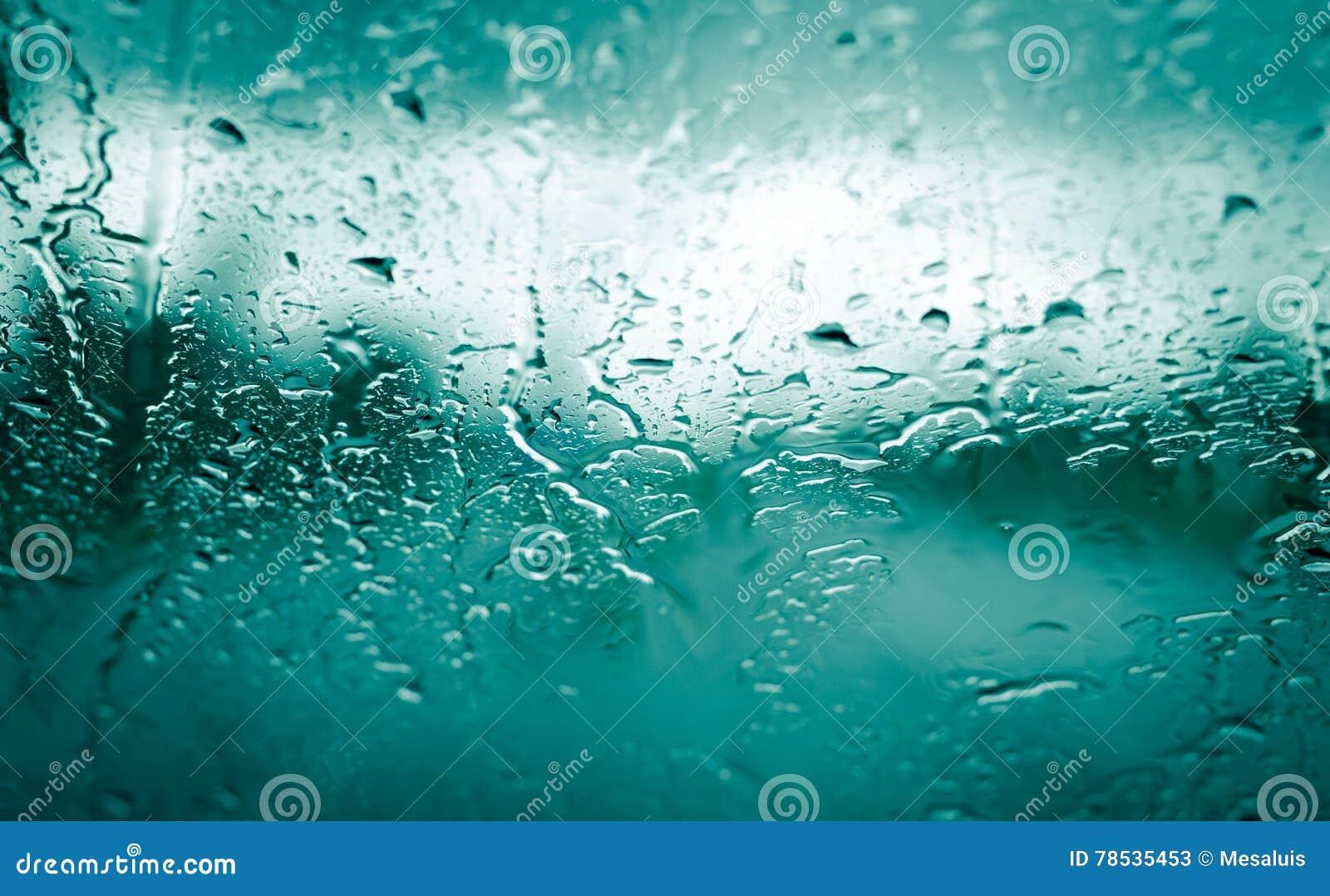 Baisses de pluie sur le verre vert de voiture avant