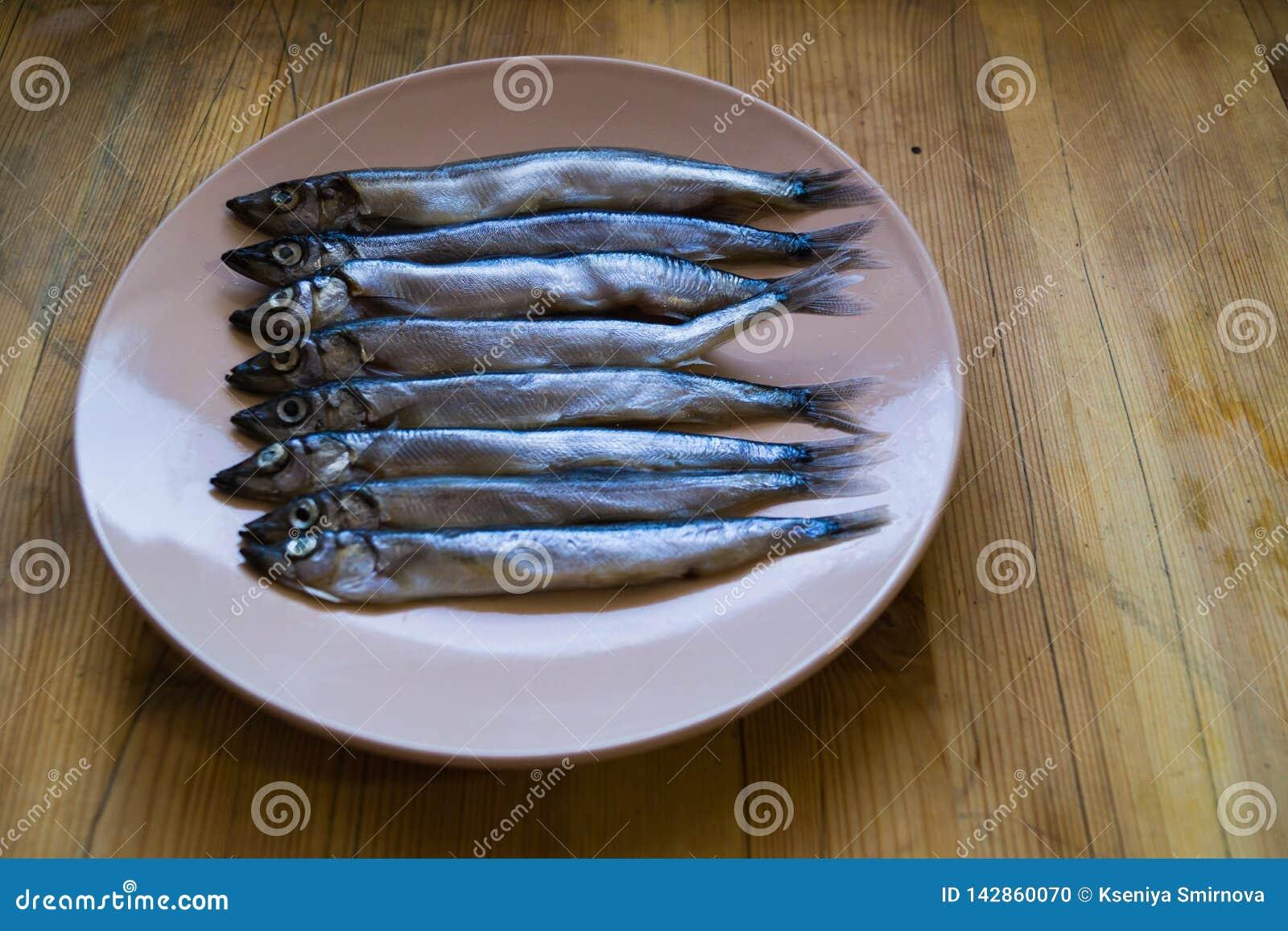 Baixa opinião lateral peixes de prata pequenos em uma placa bege em uma tabela de madeira, fim acima