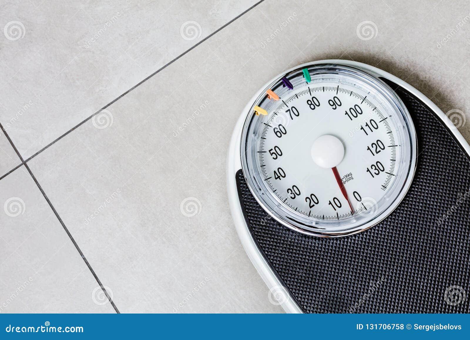 Baixa seção do homem que está na escala do peso