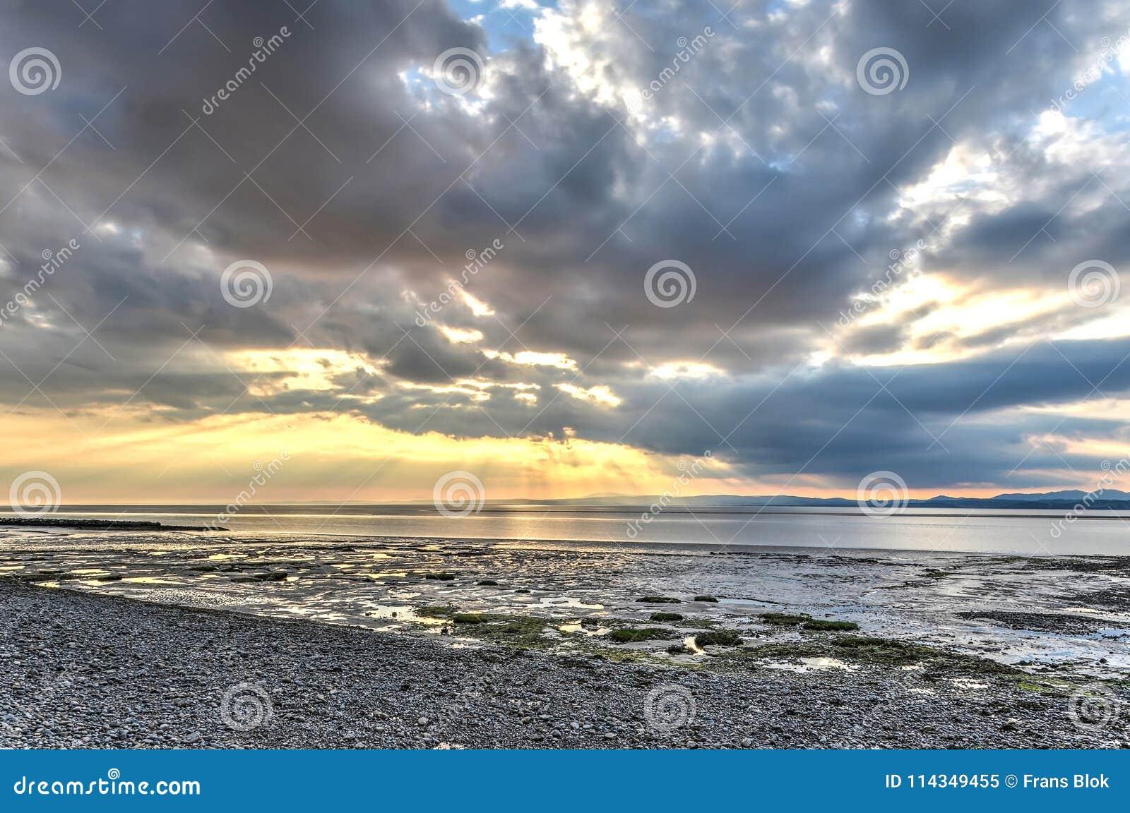 Baixo sol que quebra através das nuvens em Morecambe