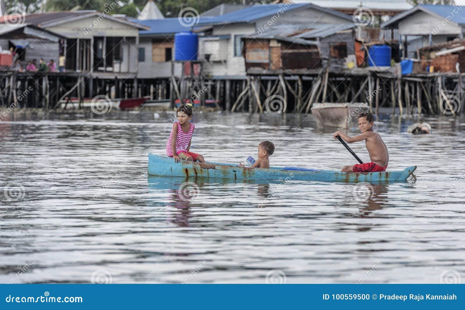 Bajau部落孩子获得乐趣通过荡桨小船在他们的村庄房子附近在海,沙巴Semporna,马来西亚