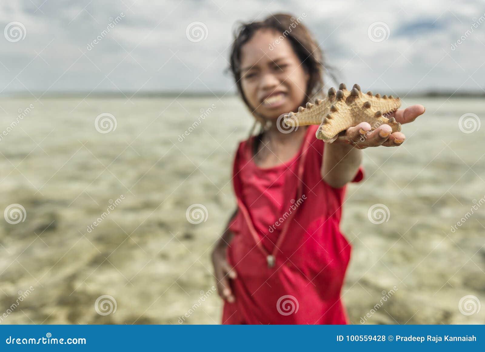 Bajau-Stammmädchen hob Sternfische vom Meer und das Versuchen auf, das an Touristen, Sabah Semporna, Malaysia zu verkaufen