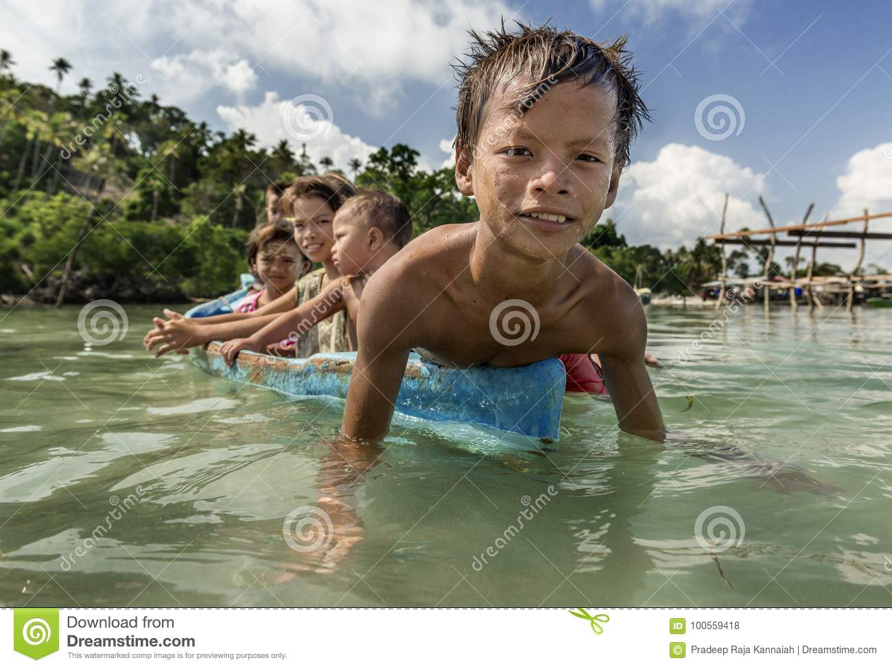 Bajau tribe kids having fun by rowing small boat near their village houses in Sea, Sabah Semporna, Malaysia