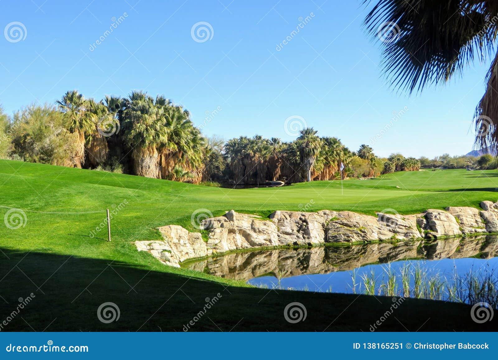 Bak den gröna sikten av ett härlig golfhål och gräsplan som omges av palmträd och ett damm i Palm Springs, Kalifornien
