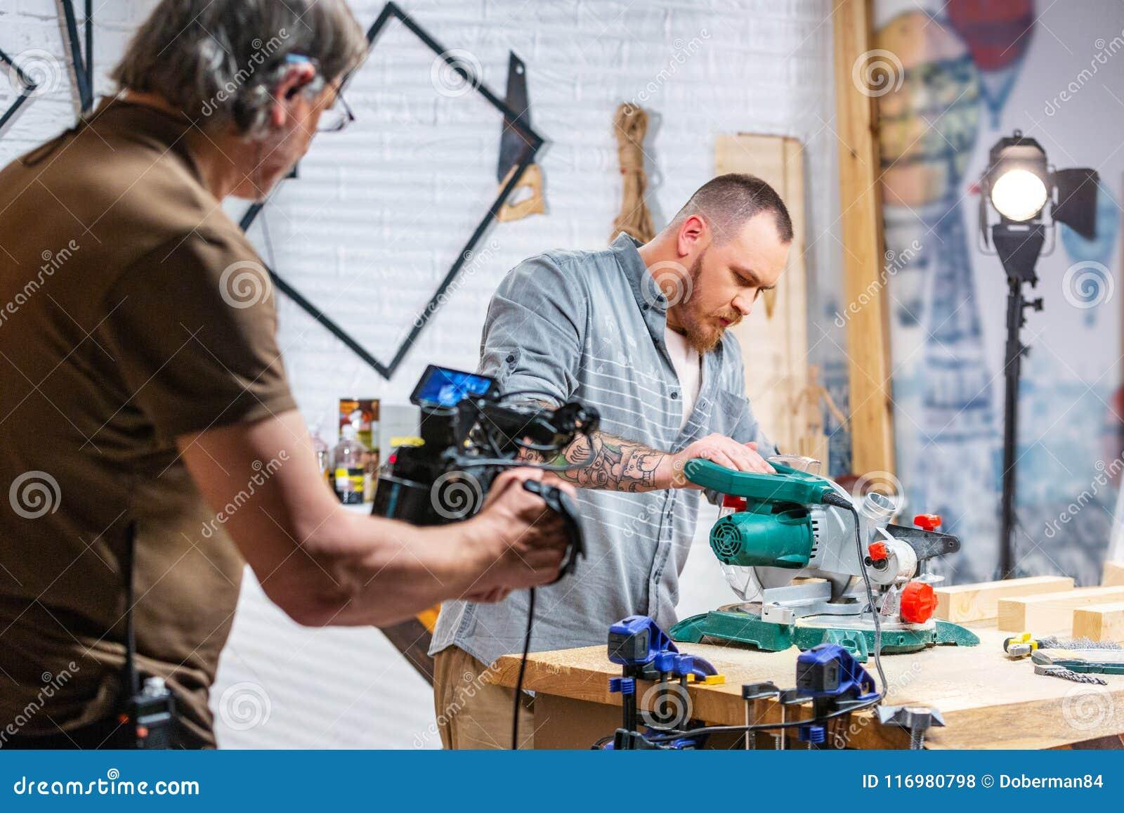 Bak platserna av produktion för video skytte för kamerautrustning den fastställda platsen med arbetaren