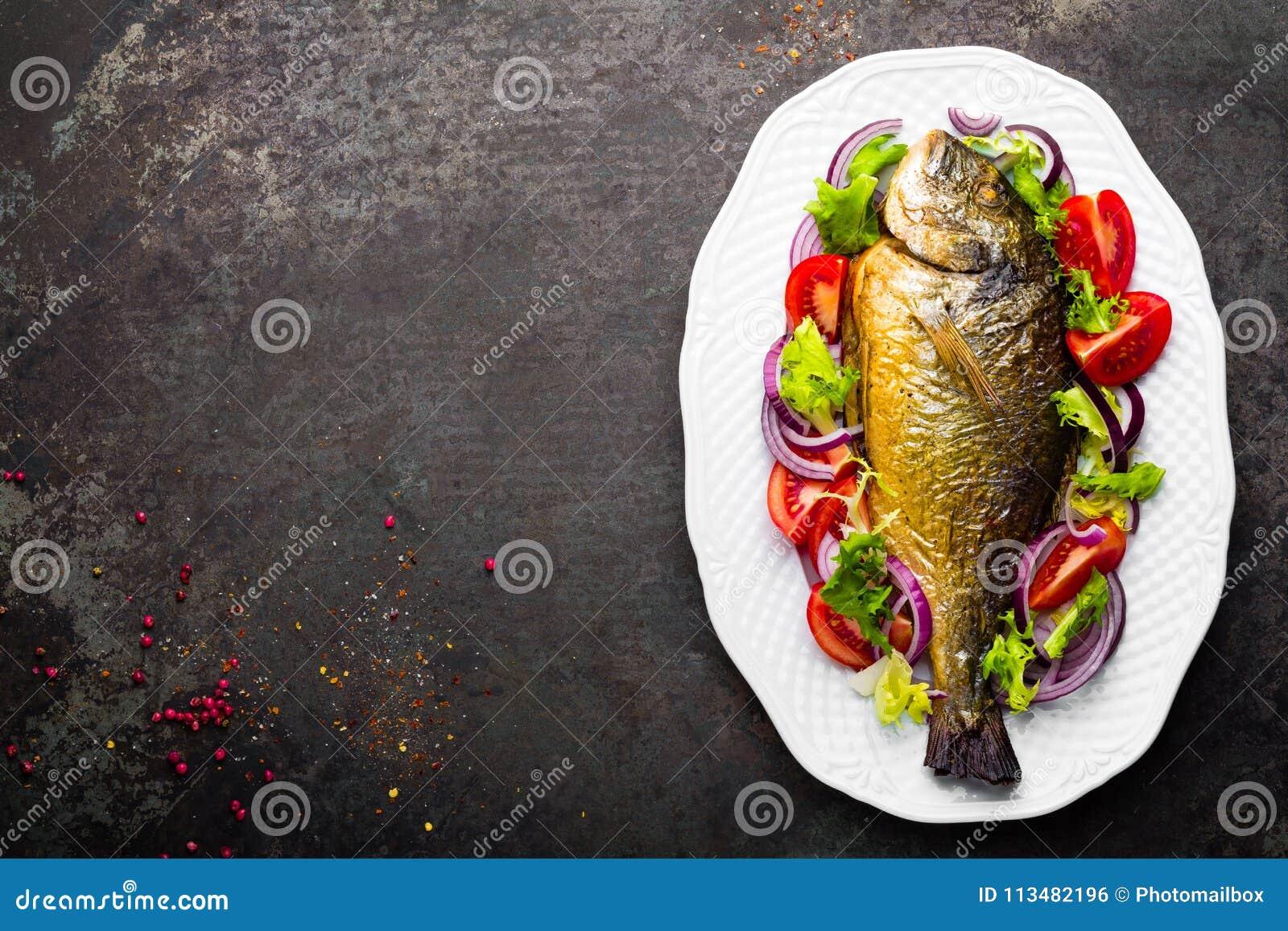 Bakad fisk Dorado Sallad för bakad och ny grönsak för Dorado fiskugn på plattan Havsbraxen eller grillad doradafisk och grönsaksa