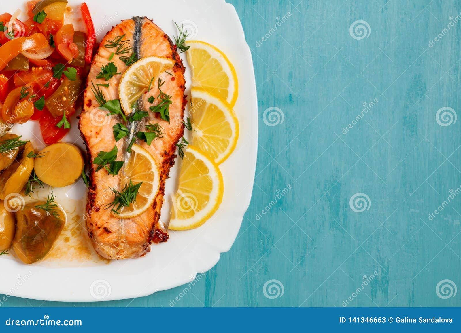 Bakad laxfilémedaljong med sallad av inlagda grönsaker och champinjoner på en vit platta på en blå bakgrund, bästa sikt,
