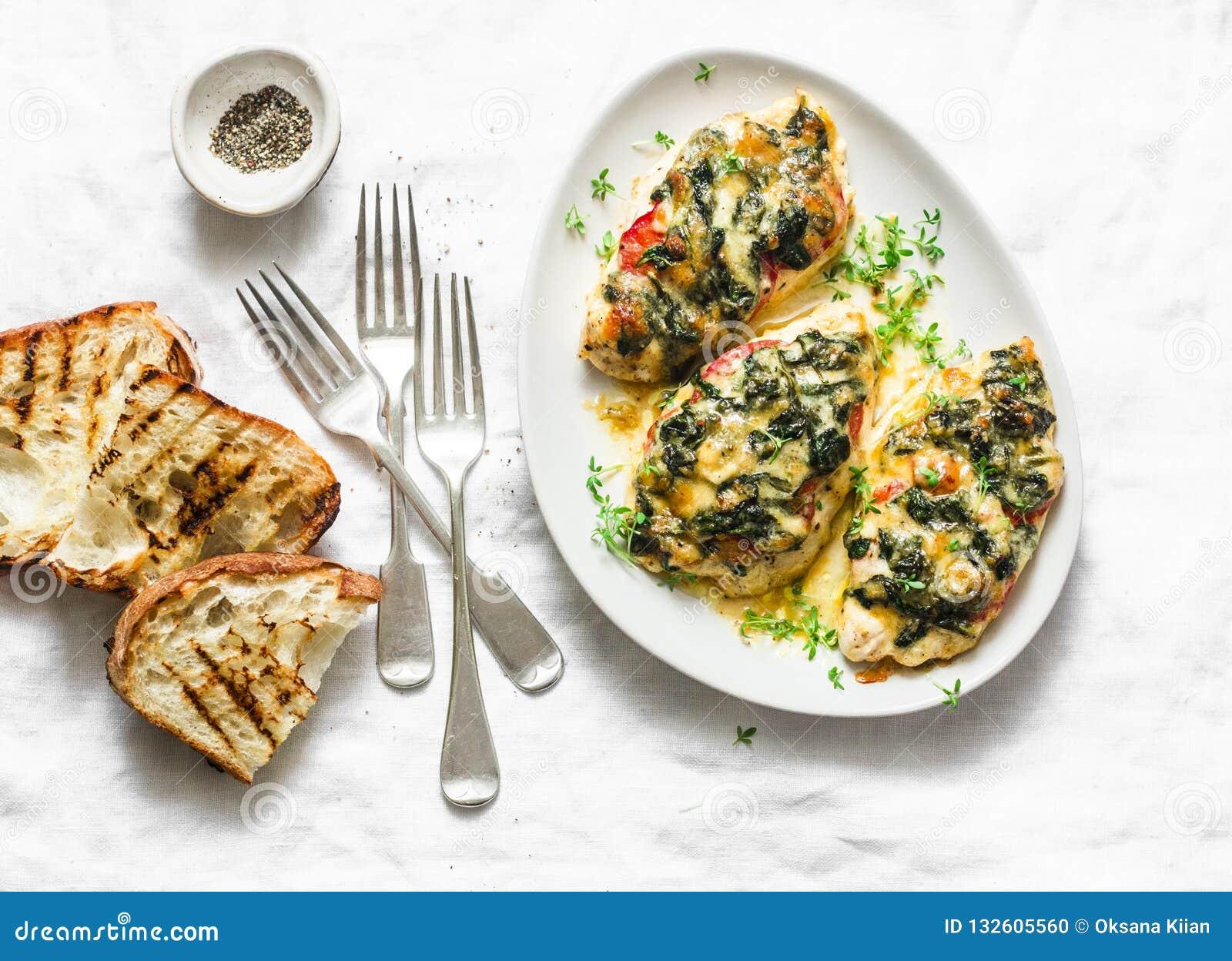 Bakat fegt bröst med den läckra tomater, spenat och mozzarellaen - banta lunch i medelhavs- stil på en ljus bakgrund
