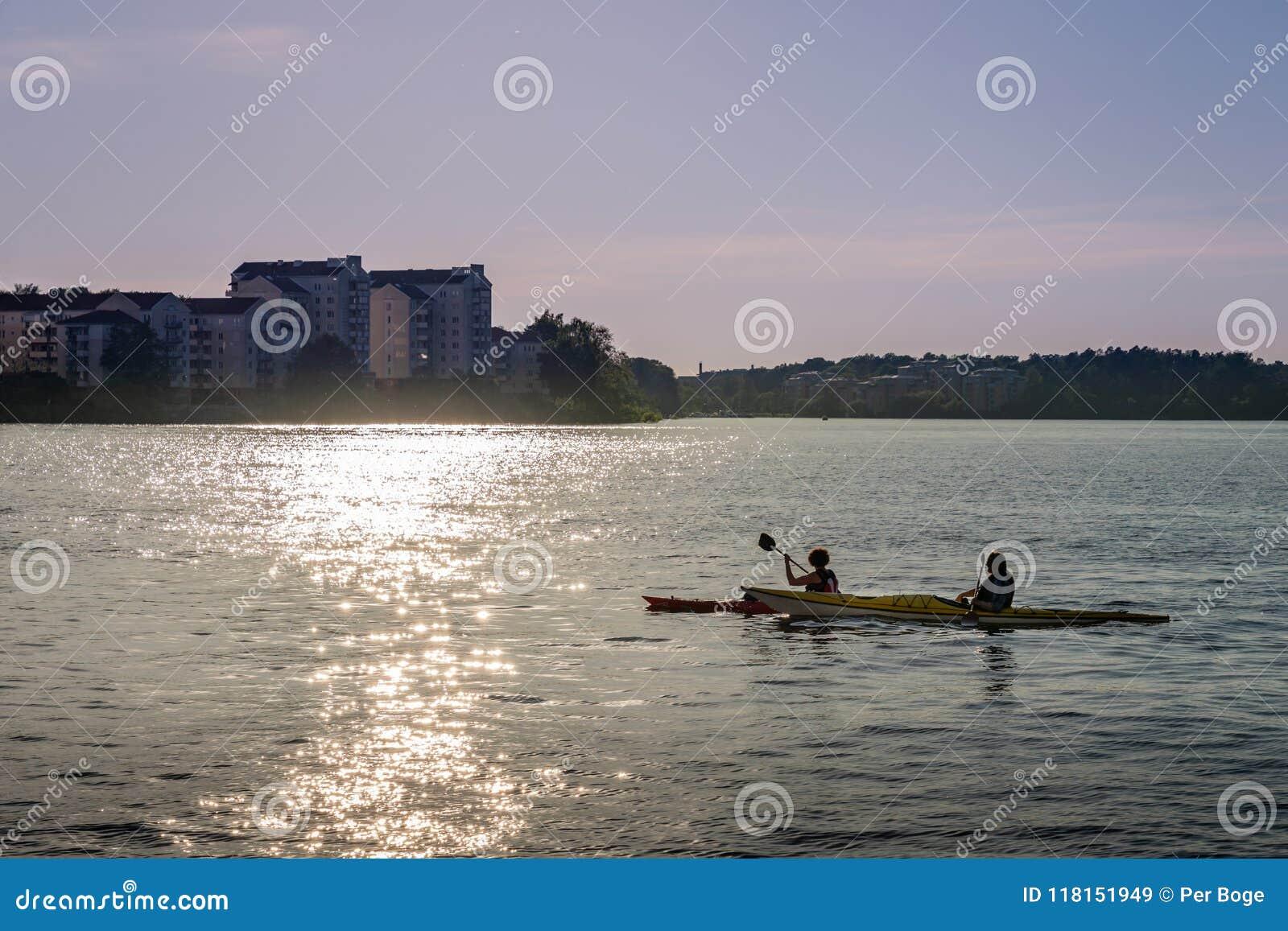 Bakbelyst solnedgångsikt av ett par som kanotar i staden